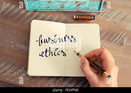 Retro effect and toned image of a woman hand writing a note with a fountain pen on a notebook - Stock Photo