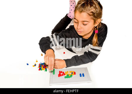 Eight year old girl playing with board game isolated on white - Stock Photo