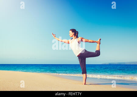 Healthy Lifestyle Concept, Beautiful young woman stretching practicing yoga on the beach - Stock Photo