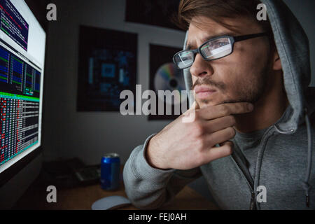 Pensive attractive young man in glasses and sweatshirt with hood thinking and coding at home - Stock Photo