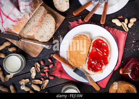 Peanut butter and jelly sandwich on a rustic table. Photographed from directly above. - Stock Photo