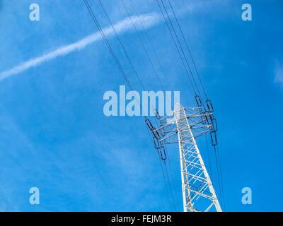 High voltage pylon against blue sky. - Stock Photo