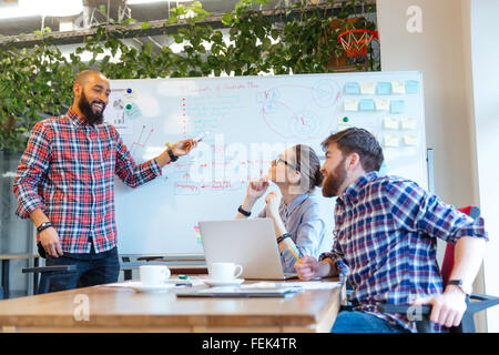 Afro american man presenting business plan to his colleagues on  meeting in office - Stock Photo