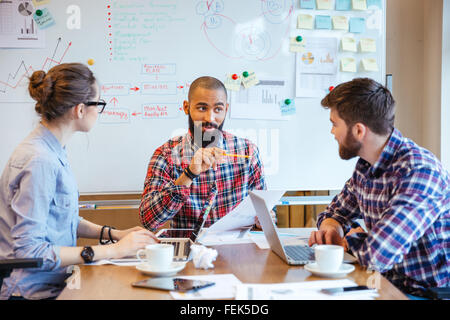 Group of creative young people making new project together in conference room - Stock Photo