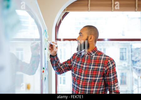 Profile of handsome african man with beard standing and writing on whiteboard - Stock Photo