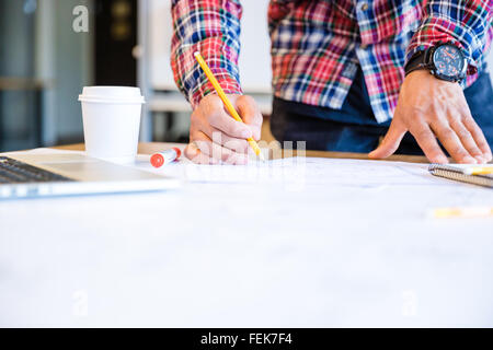 Young african american student drawing blueprint with pencil standing in classroom - Stock Photo