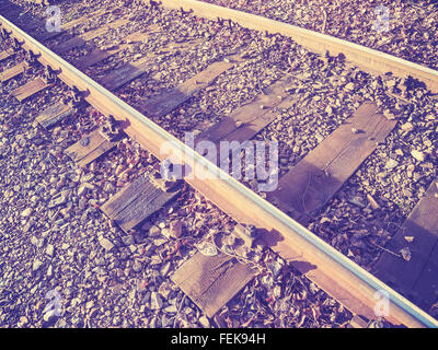 Retro filtered photo of railway tracks with wooden sleepers. - Stock Photo