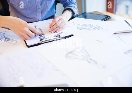 Closeup of hands of young woman fashion designer creating new collection of clothes and drawing sketches on clipboard - Stock Photo