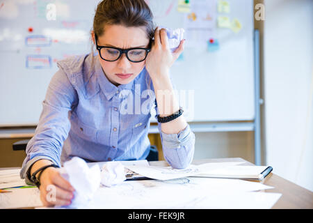 Depressed unhappy young woman fashion designer sitting and drawing sketches on workplace - Stock Photo