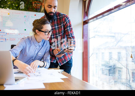 Two young woman and man fashion designers working and using tablet together - Stock Photo