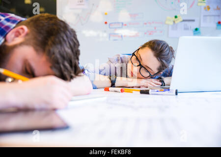 Exhausted young woman and man sleeping on the table in office - Stock Photo