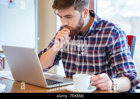 Serious focused bearded young man in checkered shirt sitting at the table and using laptop - Stock Photo