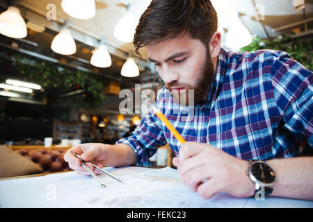 Young man engineer working on blueprint in office - Stock Photo