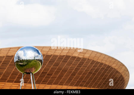 A reflective sphere sculpture with the Velodrome in the background, Olympic Park, Stratford, London, E15. - Stock Photo