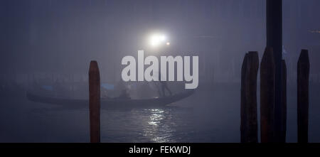 Gondola in a thick fog during nightfall in Venice, panoramic shot - Stock Photo