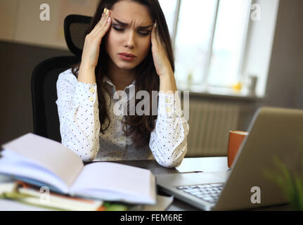 indoor picture of bored and tired woman taking notes - Stock Photo