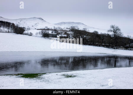 Rain forms a floodwater pond in a frozen snowy field at Crookedshaws, Scottish Border Cheviot foothills near Yetholm - Stock Photo