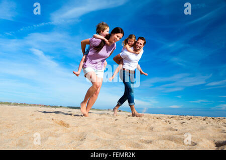 Mother and father piggybacking their son and daughter on the beach - Stock Photo