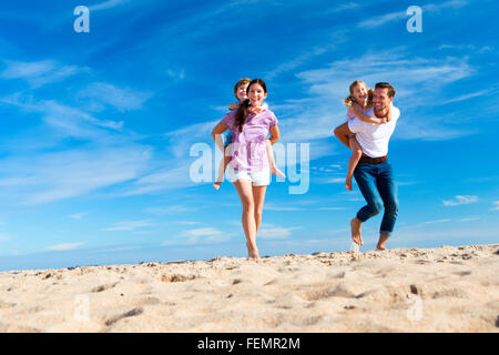 Mother and father piggybacking their son and daughter on the beach. - Stock Photo