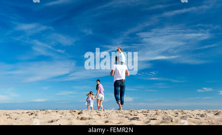 Family of four walking down to the coast. The little boy is on the fathers back and is waving at the camera. - Stock Photo