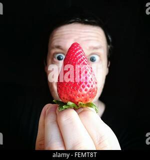 Portrait Of Man Holding Strawberry Against Black Background - Stock Photo