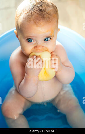 Messy baby in the bath, trying to eat a sponge. - Stock Photo