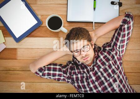 Composite image of hipster wearing eye glasses lying on hardwood floor - Stock Photo