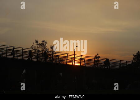 Low Angle View Of Silhouette People Walking On Bridge Against Sky At Sunset - Stock Photo