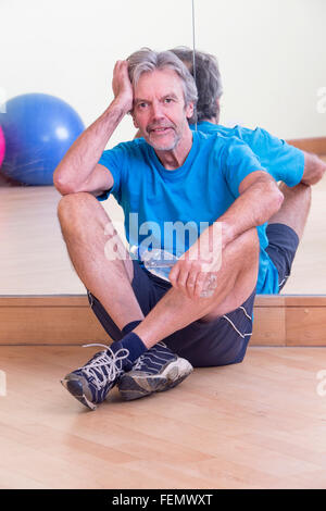 Senior man relaxing after his workout in the gym - Stock Photo