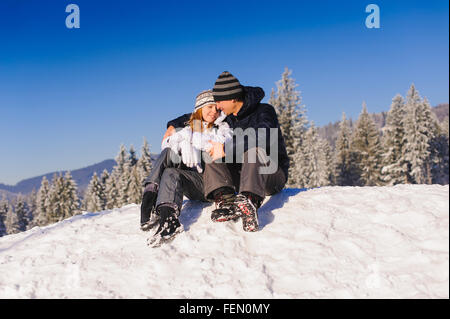 Happy couple embracing tenderly in snow at ski slope in winter mountains - Stock Photo