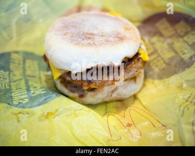 A McDonald's Sausage McMuffin with Egg breakfast sandwich. - Stock Photo