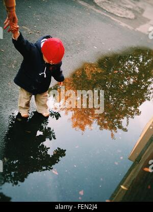 Cropped Image Of Mother Holding Baby Hand By Puddle On Street - Stock Photo