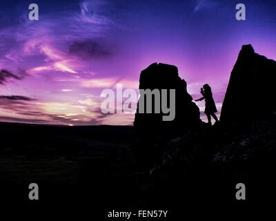 Silhouette Woman On Rocks In Dartmoor National Park At Dusk - Stock Photo