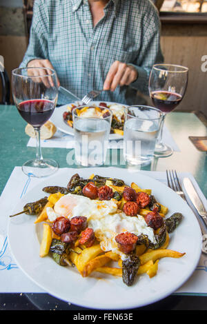 Fried eggs with chips, chorizo and Padron peppers in a restaurant. - Stock Photo