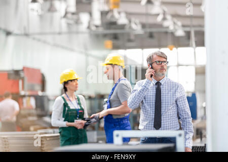 Businessman and workers in factory - Stock Photo