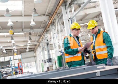 Workers in protective workwear with clipboard in factory - Stock Photo