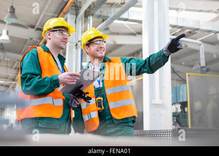 Workers in protective workwear talking with clipboard in factory - Stock Photo