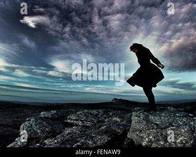 Silhouette Woman Standing On Rock Against Cloudy Sky - Stock Photo