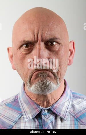 Close-Up Portrait Of Angry Man Against Gray Background - Stock Photo