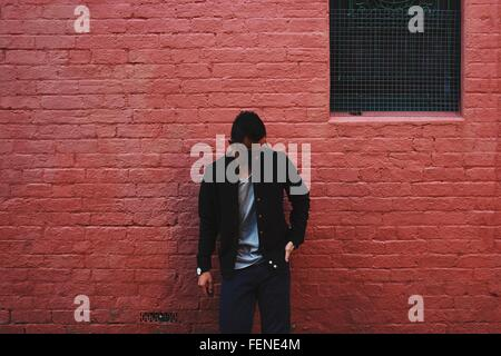 Young Man Wearing Sunglasses Standing Against Red Brick Wall - Stock Photo