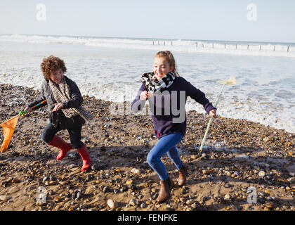 Brother and sister with nets running from ocean onto beach - Stock Photo