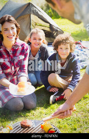 Family watching father barbecuing at campsite grill - Stock Photo