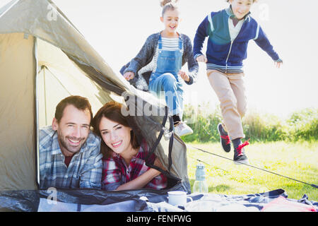Portrait smiling couple in tent with kids playing nearby - Stock Photo