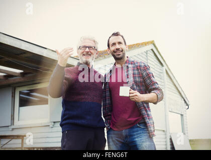 Father and son talking and drinking coffee outside house - Stock Photo