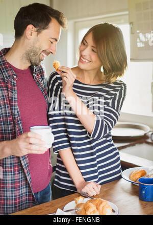Girlfriend feeding boyfriend croissant in kitchen - Stock Photo