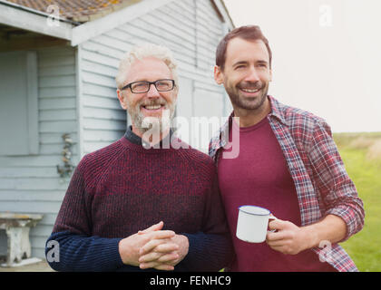 Portrait smiling father and son drinking coffee outside - Stock Photo
