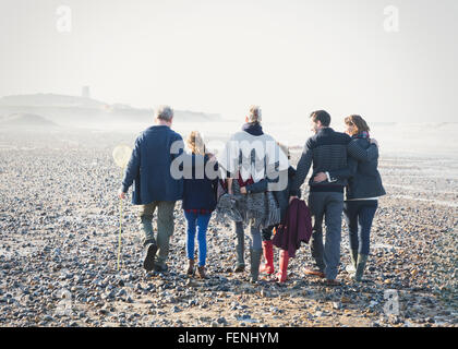 Multi-generation family walking in a row on beach - Stock Photo