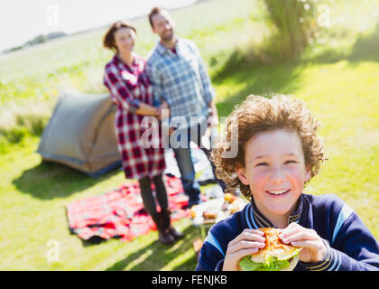 Portrait smiling boy eating hamburger with parents at sunny campsite - Stock Photo