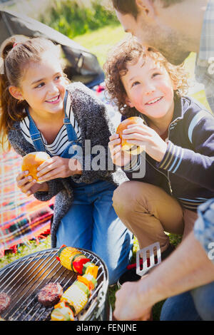Father and kids eating hamburgers at barbecue grill - Stock Photo