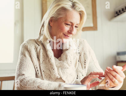 Smiling senior woman in sweater texting with cell phone in kitchen - Stock Photo